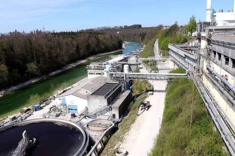 A wastewater treatment plant located next to a river in green surroundings